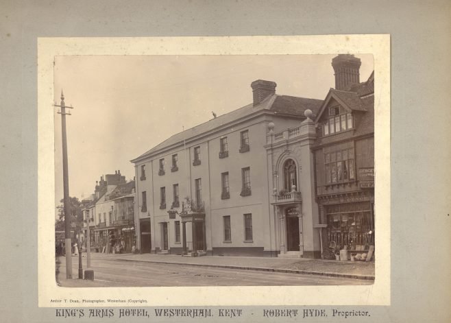 This photograph dates from the late 1890s when Robert Hyde took over from William Simpson as proprietor of the Kings Arms Hotel. By that time the discrete entrance for ladies had been built between the hotel and William Genge's Ironmongery shop. This allowed ladies staying at the hotel to enter and leave the building without having to walk through the bar.