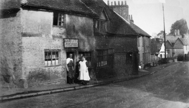 Benjamin Haylett stands in the sun outside his bootmaker's shop with his wife Isabell. It would have been very gloomy working the leather in the cottage with so few windows. Darenth Nursery shop can be seen further down the hill with its distinct white frontage and cat-slide roof. Tucked in behind the furthest of these cottages was a blacksmith's forge which was working until the 1920s.