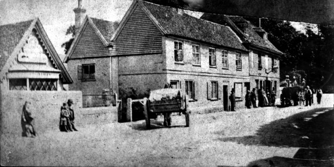 This damaged glass plate photograph dates from circa 1890 and shows three cottages that used to be attached to what was 'The Old House Inn' where the crowd are standing outside by the drayman's cart. In the foreground is the Darenth Nursery shop behind the high stone wall where the children are standing
