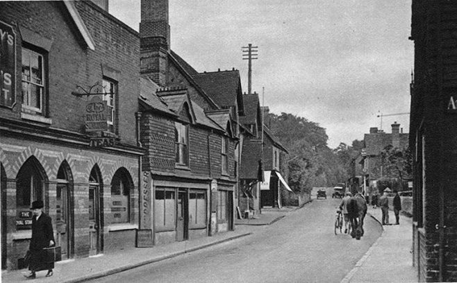 """This photograph from circa 1920 shows the right-hand end of the original 'Royal Standard' - the last pub to be opened in the town and the first to be demolished. Just beyond the pub were two shops that have also gone. The first, beside the pub, a gent's hairdressers for many years: Margaret Brown """"...I remember taking my brother for a haircut when he was tiny. Lots of boys used to go to Mr Freake at the bottom of Vicarage Hill, but I used to take him to Mr Stanton's little barbers shop by the 'Royal Standard' in the High Street. Townsend's shoe shop was on the corner of New Street and there was a funny little tea shop next door called 'Gutsell's' and then Bert Stanton's gent's hairdressers was on the other side of that. I had to take him during the week though, as he wouldn't do boys on a Saturday, that was reserved for the working men."""" The adjoining shop was a tobacconist and newsagents run by William and Lily Bowra. Beyond that the imposing frontage and porch of the Public Hall can be seen."""