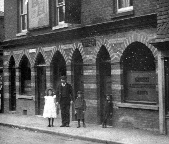 This charming photograph can be fairly accurately dated at around 1904 as the brewer's promotional slogan in the window advertises 'Blighs Superior Sevenoaks Ales' which were about to disappear as the Sevenoaks Brewery had been bought out by Ben Bushell of Westerham's Black Eagle Brewery. The notice perched above and between the polychromatic brick arched doorways stated 'Good Stabling To Let'.  The little boy who has assumed a rather jaunty pose against the doorway doesn't feel like he is part of the family standing together. He is somewhat more smartly dressed with his suit and little felt hat and what is either a handkerchief or a buttonhole flower - a bit of a rebel stealing attention perhaps...?