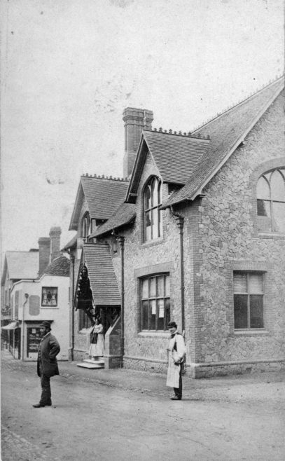 Walking on past the Public Hall and looking back would give the view shown here in another 'posed' photograph circa 1904. Many working men wore a bowler hat at that time. The man in the white apron is likely one of Charles Hooker's printers from the 'Herald Steam Printing Works' just out of shot on the right of the photograph.  The lady on the steps of the Hall is Fanny Goodfellow, the live-in Hallkeeper at that time, and just beyond the Hall can be seen the corner windows of Bowras' tobacconists shop.