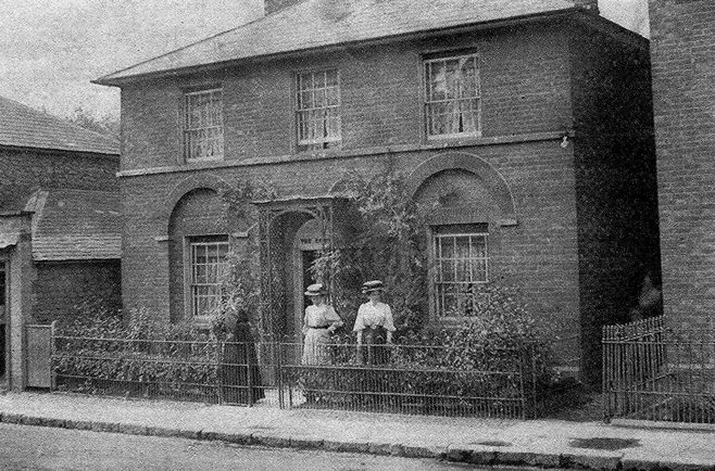 This first picture shows Ellen King enjoying the sunshine with her daughters Eva and Ethel outside 'The Cottage' circa 1908. This house is unmistakeable today, even having kept its metal railings. Only the charming pergola has gone, though there are still roses round the door.