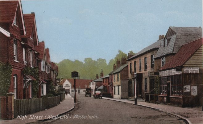 Walking further up the road into town circa 1910, a look back down the High Street to the forge on Verralls corner would reward the onlooker with the view shown here in an aquatint photo-postcard. Foreground right is Edwin Woods saddlery and the Warde Arms, while on the left opposite the Warde Arms can be seen half of the word 'Garage' with an 'AA' sign above it. This was G. T. Taylor's garage, set back from the pavement on the site now occupied by 'General Wolfe House' a modern office complex still set back from the pavement with workers' car parking in front.