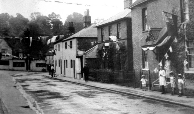 This photograph, and the next one, date from May 12th 1937 and show bunting and flags that were hung around the town to celebrate the coronation of George VI and Elizabeth on that day. Just before the bend on the right hand side of the road can be seen four brewery cottages. Within five years from when this photograph was taken this row of four cottages would be reduced to two when part of a stick of bombs landed there.