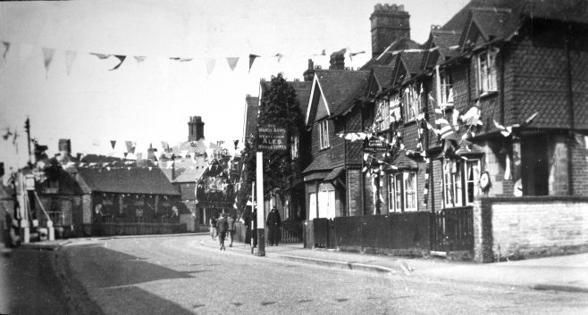 Looking back towards the town we see the High Street festooned with bunting and flags. The second house in on the right hand side has a sign projected from the front windows saying 'MODEL LAUNDRY - Dyeing & Cleaning'. This was the business of William Burgess and his wife Agnes who worked in a large shed in the back garden of this domestic house with their son Robert who was just sixteen at that time. On the extreme left of the photograph can just be seen the boundary wall of A. C. (Charlie) Sharp's garage, one of two at this end of town, and competition for Charles Woolletts' Westerham Motor Garage just out of frame on the extreme right of this picture.