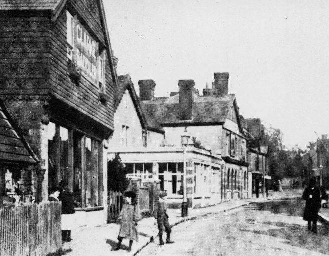 Further up the High Street this 'posed' photograph dates from circa 1909 and shows the entrance of New Street on the left just before the single-storey shops that still exist today. In the foreground, George Clarkes' Saddlery is today a Dental Spa. The first shop on the corner of New Street is that of Henry Edgar Townsend, bootmaker and dealer. The next shop is 'Hope Cottage Bazaar' run by Mary Garratt, purveyor of 'bright tinware and other bazaar items'. The large building just beyond the two single-storey shops was the original Victorian 'Royal Standard' pub as can be seen in the following two photographs...