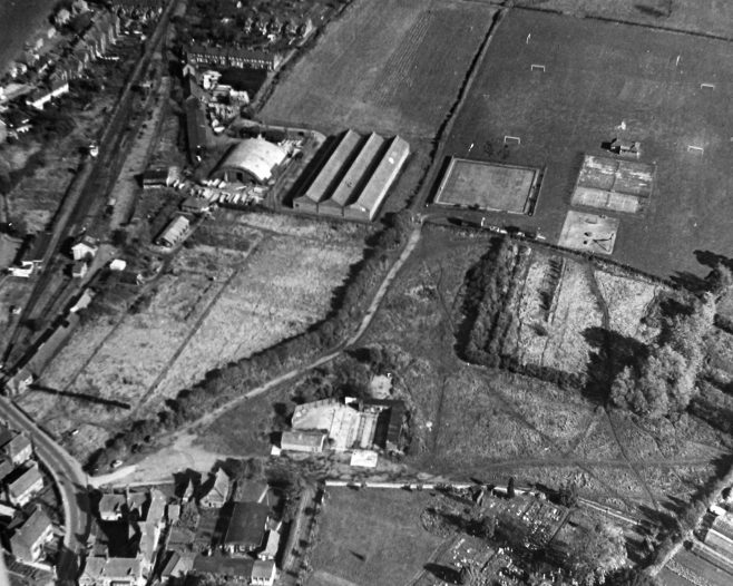 This aerial photograph from the 1940s shows the large Nissen Hut and three long sheds that collectively were the Ministry of Supply 'Buffer Depot' beside the railway used for storing consumables on ration. To the right of the long sheds can be seen the Bowls Club's new bowling green yet to acquire a clubhouse. Just below and to the right of the picture, John Hollingworth's nursery field, known to locals as 'Hollybob's Ranch'. Below that, in the centre of the picture is the Cattle Market and livestock pens, and the curve-roofed building below the market is the Women's Institute with the Girl Guide's hut attached on the right hand side.