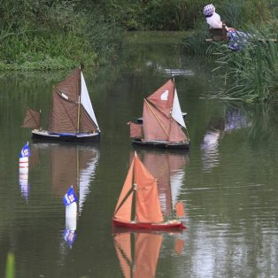 Radio-controlled model boats cruise around the marker buoys at Long Pond